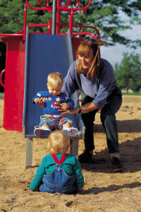 Woman and two children playing on a playground