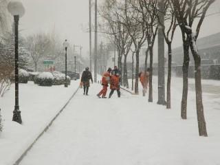 several men shovel sidewalk