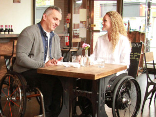 Couple sits in wheelchairs at cafe