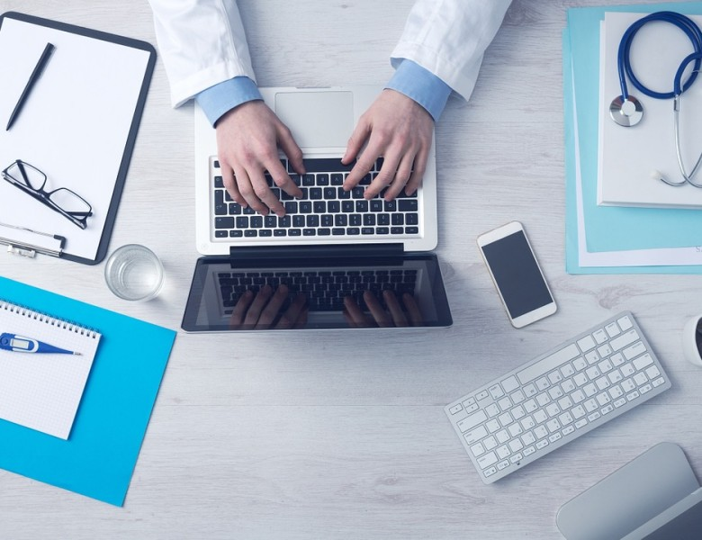 doctor types at laptop computer