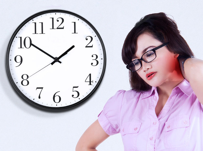 A woman with a pained expression holds her neck beside a large analog clock face