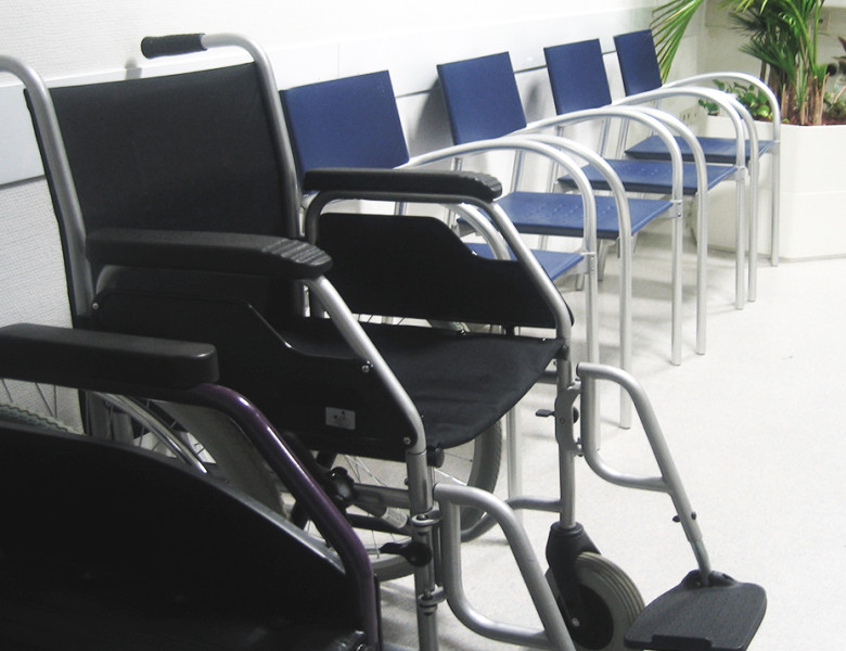 A wheelchair next to a row of plastic chairs