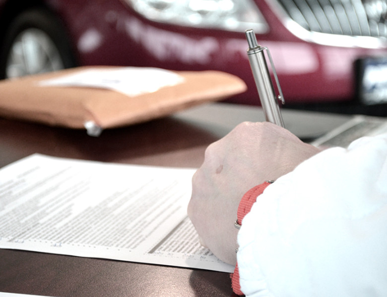 a hand signs a form with a car in the background