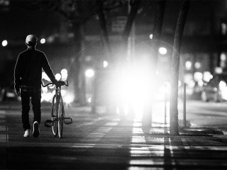 Man walks bicycle on sidewalk