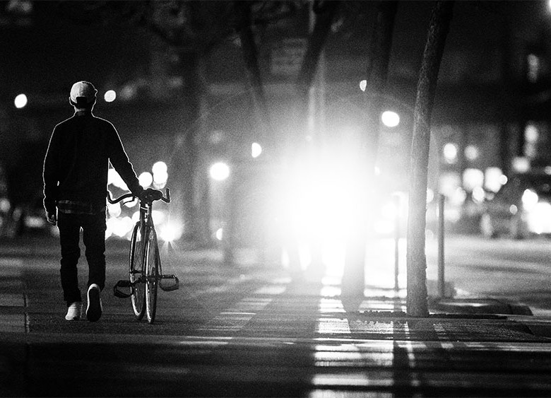 Man walks bicycle on sidewalk