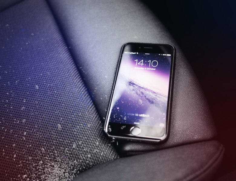 phone sits on car seat with broken glass