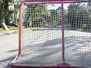 a road hockey net stands before an empty residential street