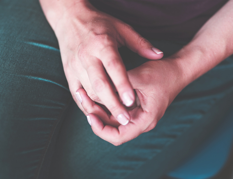 Hands nervously held together on the lap