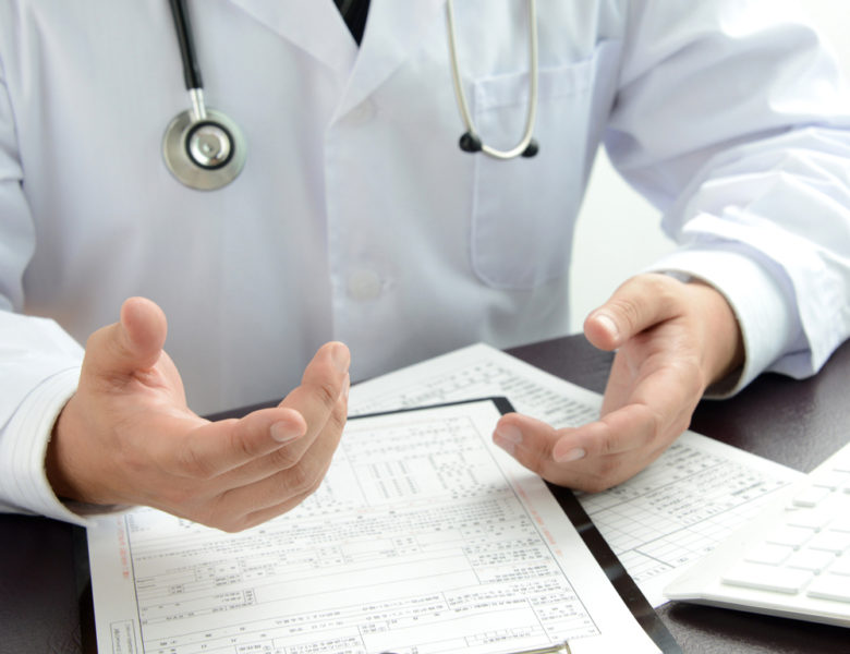 Doctor gesticulates over printed health records