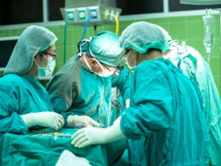 Doctors in surgery around patient